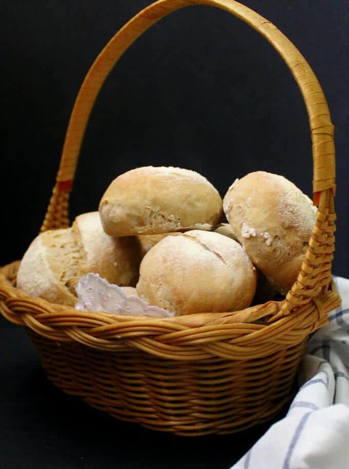 Crusty Sourdough Dinner Rolls in a wicker basket with a blue and white kitchen napkin against a black background