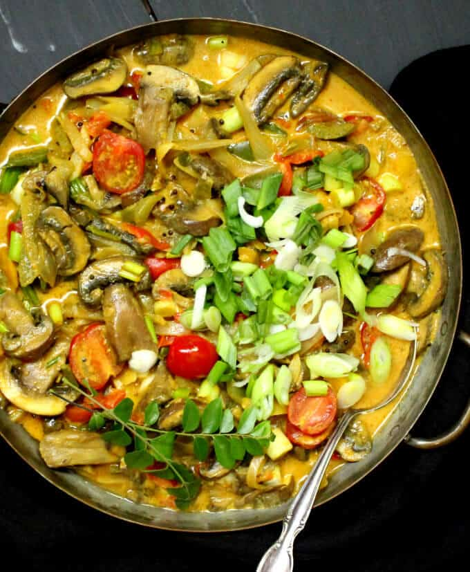 A copper pan with a colorful vegetable curry with cherry tomatoes, mushrooms, scallions, curry leaves and coconut milk