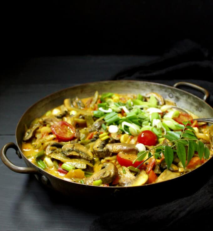 An easy and colorful and healthy creamy vegetable curry with cherry tomatoes, spring onions and mushrooms in a copper pot against a gray and black background
