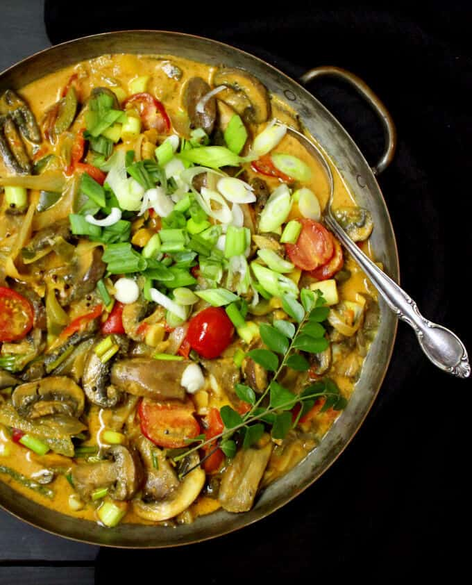 Best 20-minute Vegetable Curry with Coconut Milk, scallions, tomatoes and mushrooms with a spoon in a copper pan