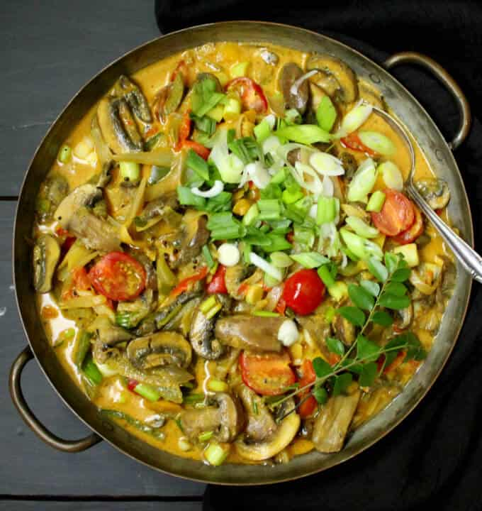 A colorful vegetable curry with coconut milk, mushrooms, scallions and curry leaves in a copper pan on a gray background