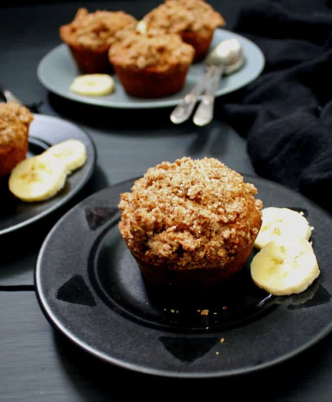 Vegan Banana Crumb Muffins in black and gray plates with slices of fresh banana and spoons and a black cheesecloth in the background. CowVegan.net