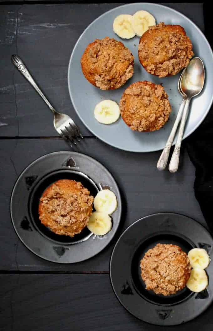 Banana streusel muffins on small black plates and three muffins on a larger gray plate with spoons, forks and slices of banana
