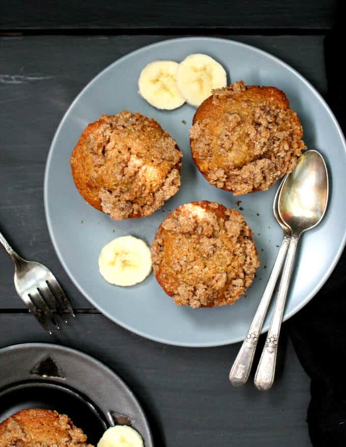 Vegan Banana Crumb Muffins in a gray plate with sices of banana and a fork and spoons