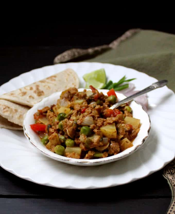 Vegan keema masala in a bowl on a white plate with rotis, onions, chile peppers and lime.