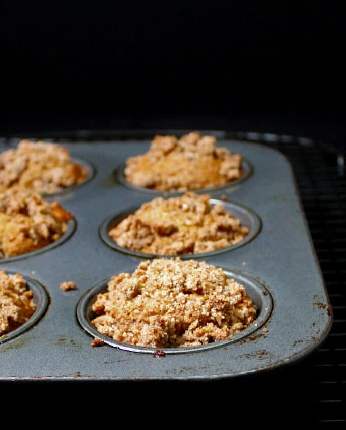 Vegan Banana Crumb Muffins with streusel in a muffin pan on a black background