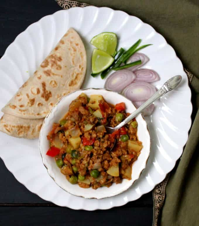 A white ceramic bowl with vegan keema masala with rotis, onions, lime and green chile peppers on a white plate.