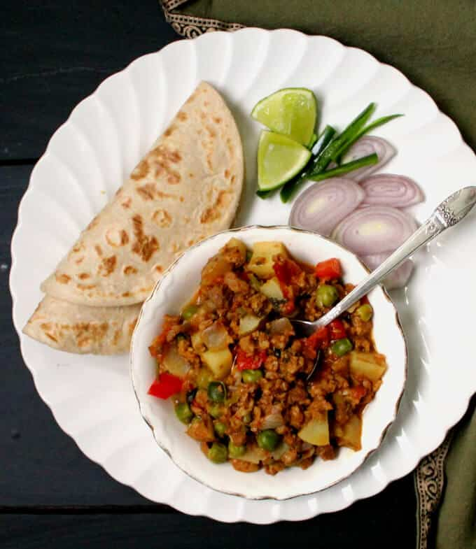Vegan Keema Recipe, spicy meatless kheema, in bowl on white plate with rotis, onions, chiles and lime.