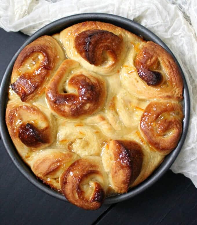 Vegan orange rolls baked in a 9-inch cake pan with an orange marmalade glaze.