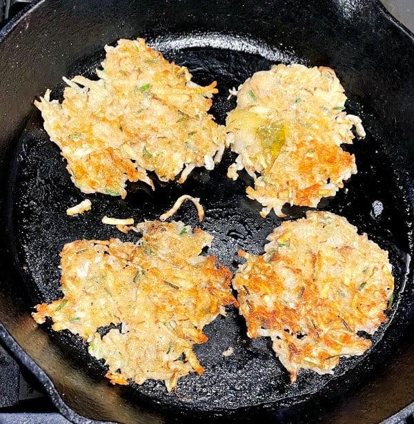 Vegan potato sauerkraut latkes fying in cast iron pan