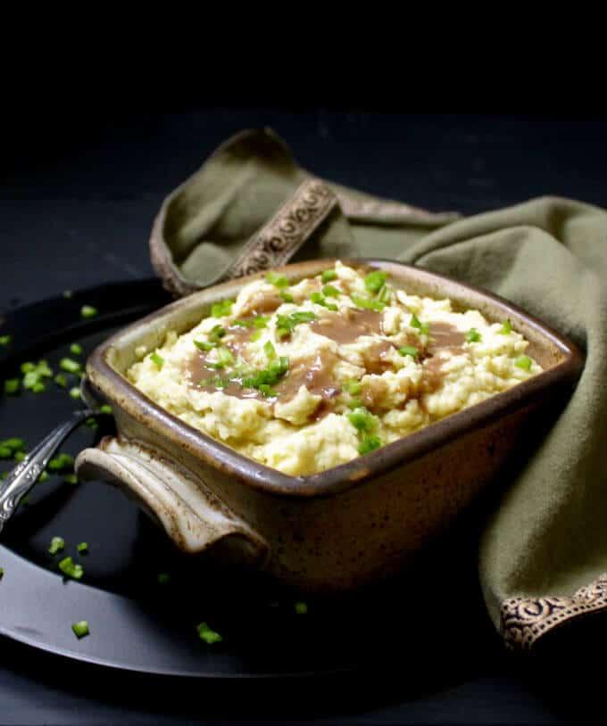 Front shot of vegan mashed potatoes in brown rectangular bowl.