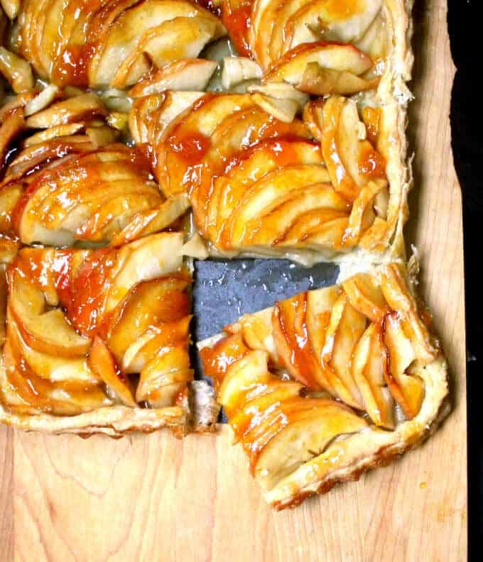 An elegant and easy French Apple Tart that looks deceptively complex, but comes together in less than 20 minutes. Sliced apples are arranged on a golden puff pastry base and all of this deliciousness is amped up by an apricot glaze. A vegan, soy-free and nut-free recipe.. #vegan #Thanksgiving #soyfree #nutfree #apple #pie HolyCowVegan.net