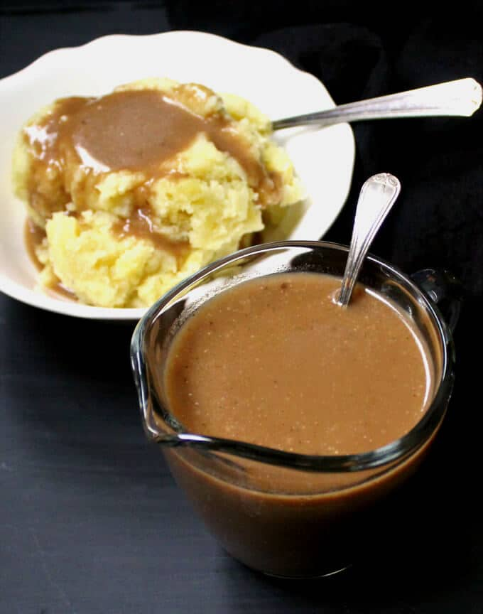 Photo of vegan mushroom gravy in a glass sauceboat with a white bowl of mashed potatoes in a white bowl with gravy poured over it in background.
