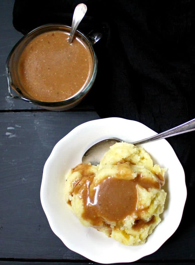 Photo of vegan mushroom gravy served over mashed potatoes in a white bowl with a spoon, with a sauce boat of gravy on the side.
