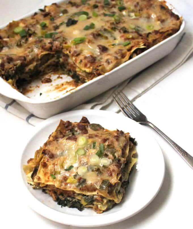 A slice of a creamy Vegan Sausage Breakfast Lasagna with the full baking tray with the baked lasagna