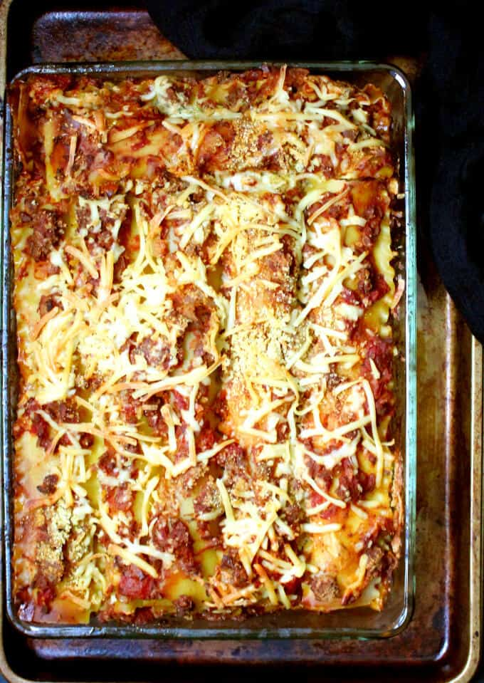 Closeup overhead shot of classic vegan lasagna in a glass baking dish layered with meaty marinara, dairyfree ricotta and cashew parm and doused with vegan mozzarella cheeze on a baking sheet against a black background.