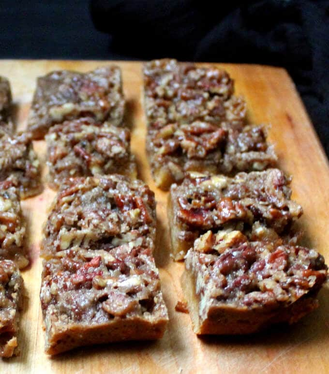 Glutenfree vegan Pecan Pie Bars. The crunch of pecans, gooey caramel and a melt-in-the-mouth almond flour crust make these the best pecan bars you've ever tasted. #vegan #glutenfree #holidays #pecanpie #cookies