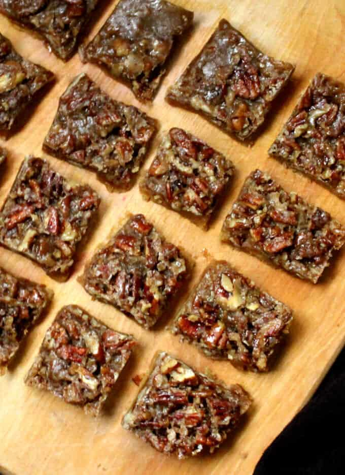 Cut squares of gf and vegan pecan bars on a wooden chopping board