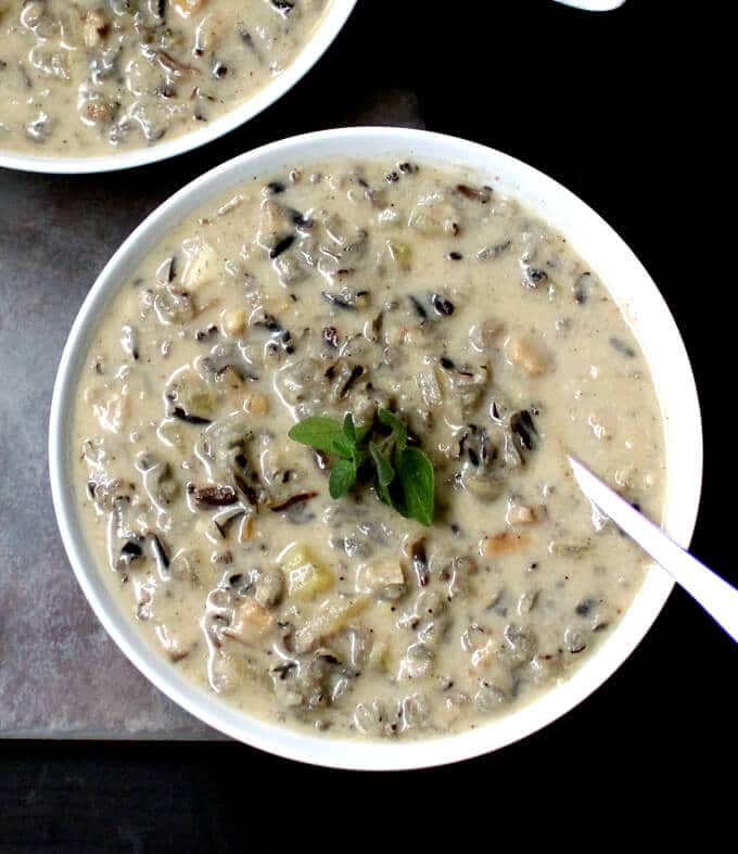 A wild rice and mushroom bisque with a soup spoon in a white bowl with a grey and black background.