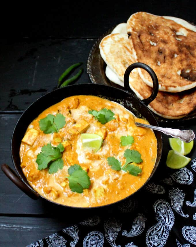 A black kadhai bowl with a fiery orange vegan butter chicken with tofu cubes floating in it, garnished with cashew cream and cilantro. Next to it are vegan naan, wedges of lime, green chili peppers and a black and white paisley print napkin on a black-blue background.