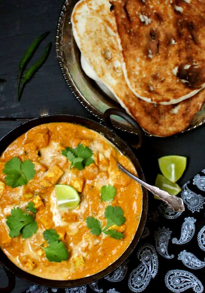 Photo of vegan butter chicken made in the Instant Pot and served in a black kadhai bowl. The sauce is garnished with cashew cream and cilantro and next to it are vegan naan, wedges of lime and green chili peppers.