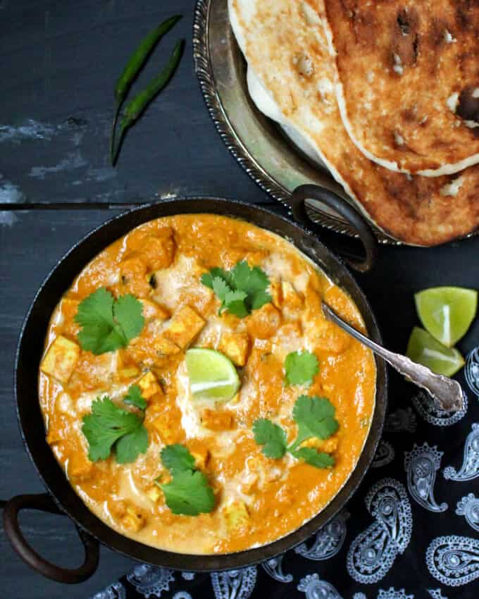 A black kadhai bowl with a fiery orange vegan butter chicken with tofu cubes floating in it, garnished with cashew cream and cilantro. Next to it are vegan naan and a black and white paisley print napkin on a black-blue background.