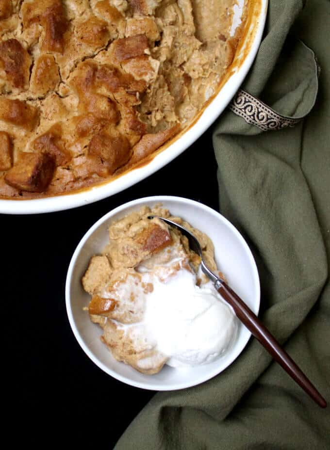 A bowl of vegan pumpkin bread pudding in a white bowl with ice cream and a spoon.