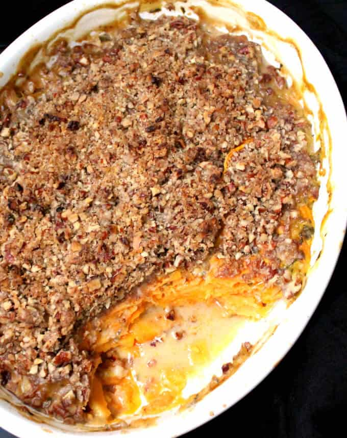 Vegan Scalloped Sweet Potatoes with Crunchy Pecan Topping in a white oval baking dish.