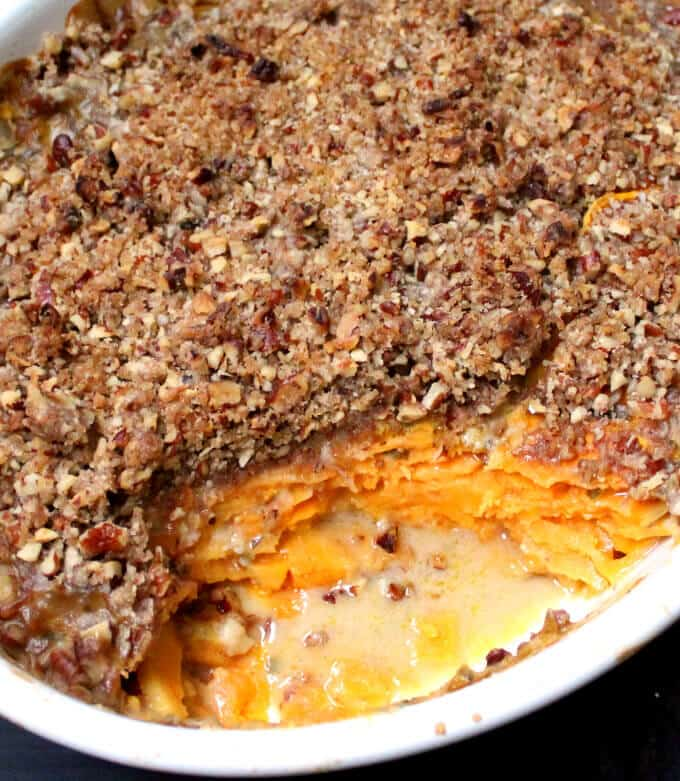 Close up of Vegan Scalloped Sweet Potatoes with Crunchy Pecan Topping in a white oval baking dish.