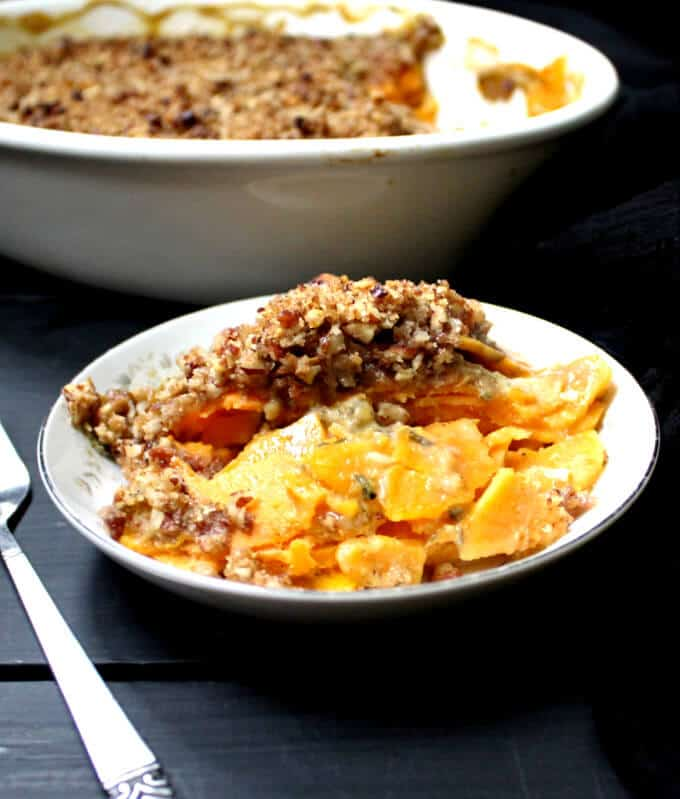 Vegan Scalloped Sweet Potatoes with Crunchy Pecan Topping in a white bowl with fork.
