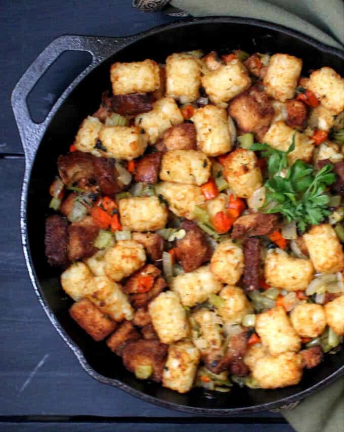 The secret to my perfect Vegan Thanksgiving Stuffing is crunchy, crispy tater tots. This traditional holiday staple gets a fresh, new makeover in a recipe that's as easy and fun to make as it is delicious to eat. Vegan, nut-free, soy-free and can be gluten-free. #vegan #soyfree #nutfree #thanksgiving #sidedish #stuffing HolyCowVegan.net
