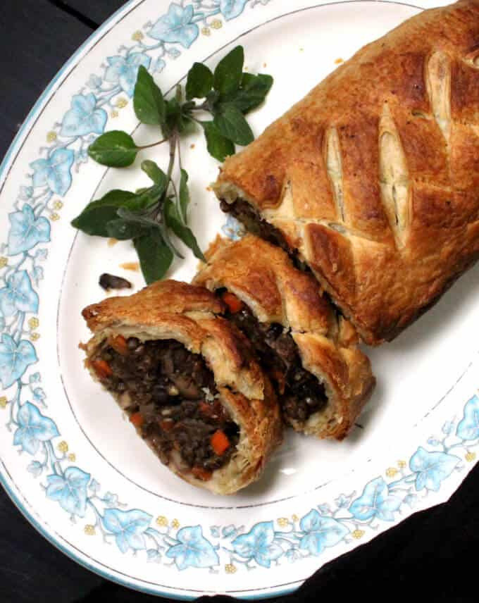 Top view of a vegan wellington with mint leaves to the side on a floral blue and white platter. Inside is stuffed a delicious stuffing of lentils and mushrooms with a mirepoix of onions, carrots and celery