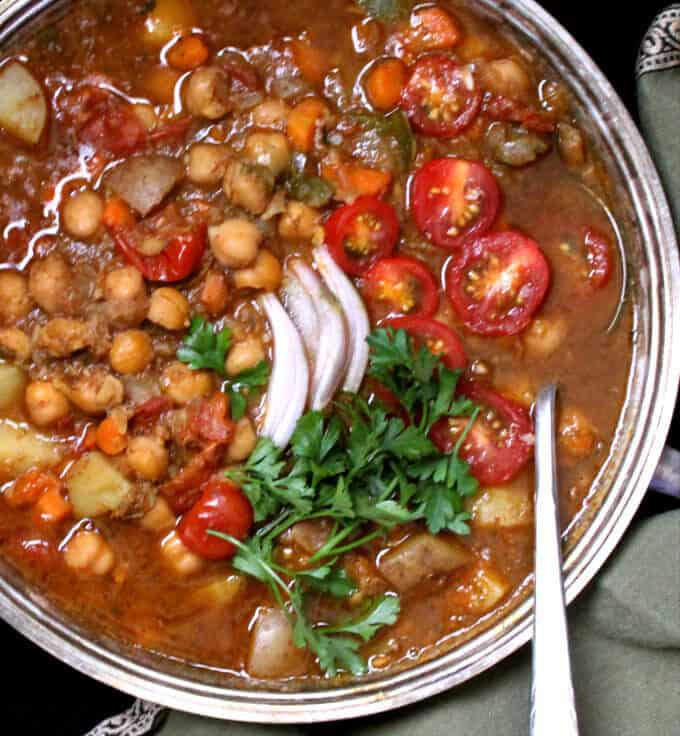 Close up shot of a Moroccan chickpea stew made in an Instant Pot pressure cooker with a silver serving spoon