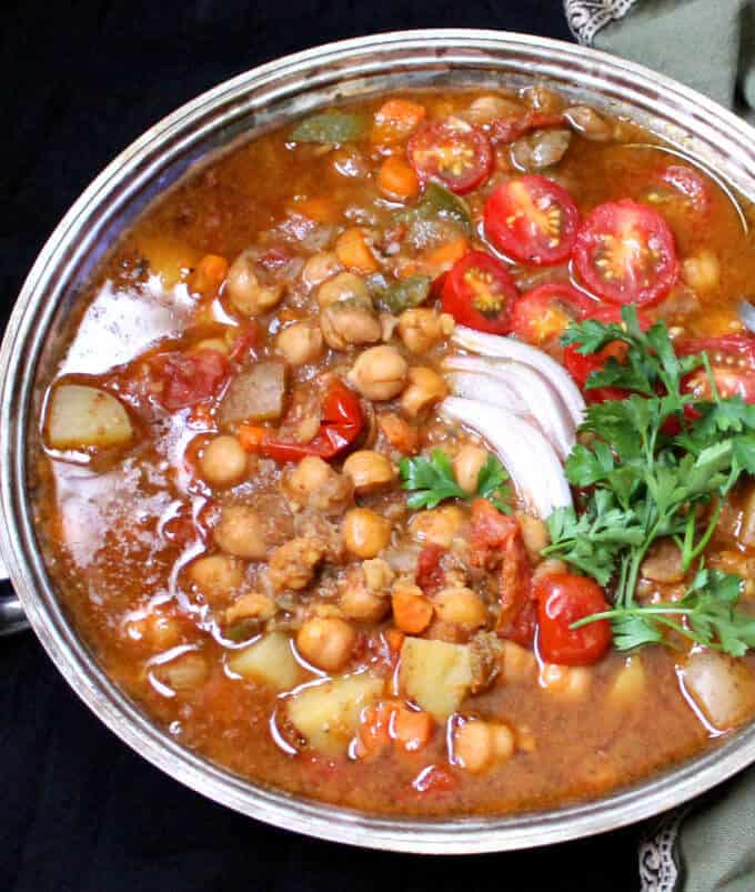 Chickpea stew in a silver server on a black table
