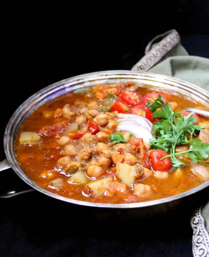 An Instant Pot Moroccan Chickpea Stew with no added oil and with chickpeas, tomatoes, carrots and potatoes in a silver server against a black background