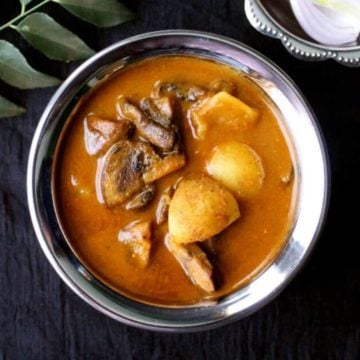 A steel and copper bowl with mushroom curry with potatoes