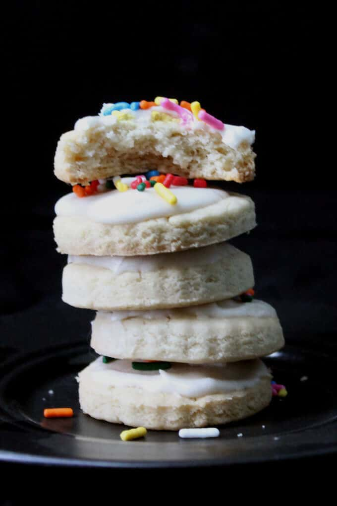These gluten-free and vegan Sugar Cookies are tender and delicious with a fluffy buttercream-like frosting. Make these a part of your holiday cookie platter. #vegan #soyfree #glutenfree #cookies #recipe #holidays HolyCowVegan.net