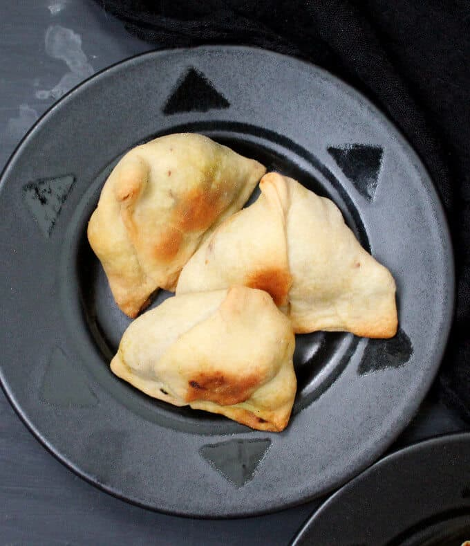 Photo of a black plate with three baked samosas.
