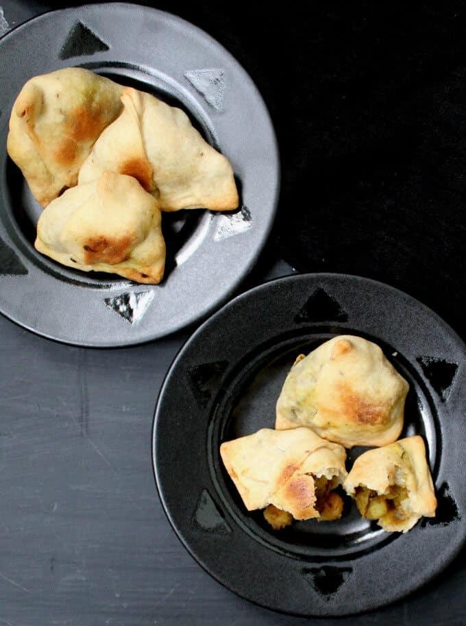 Photo of two black plates of baked samosas.