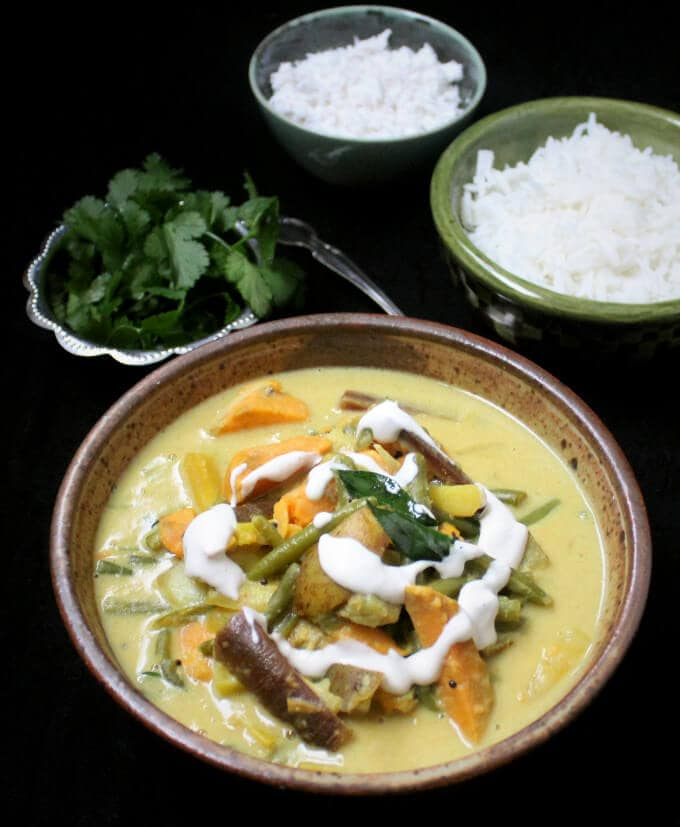 Photo of South Indian Vegetable Curry, also known as an avial, served in an earthenware bowl with coconut, rice and cilantro.