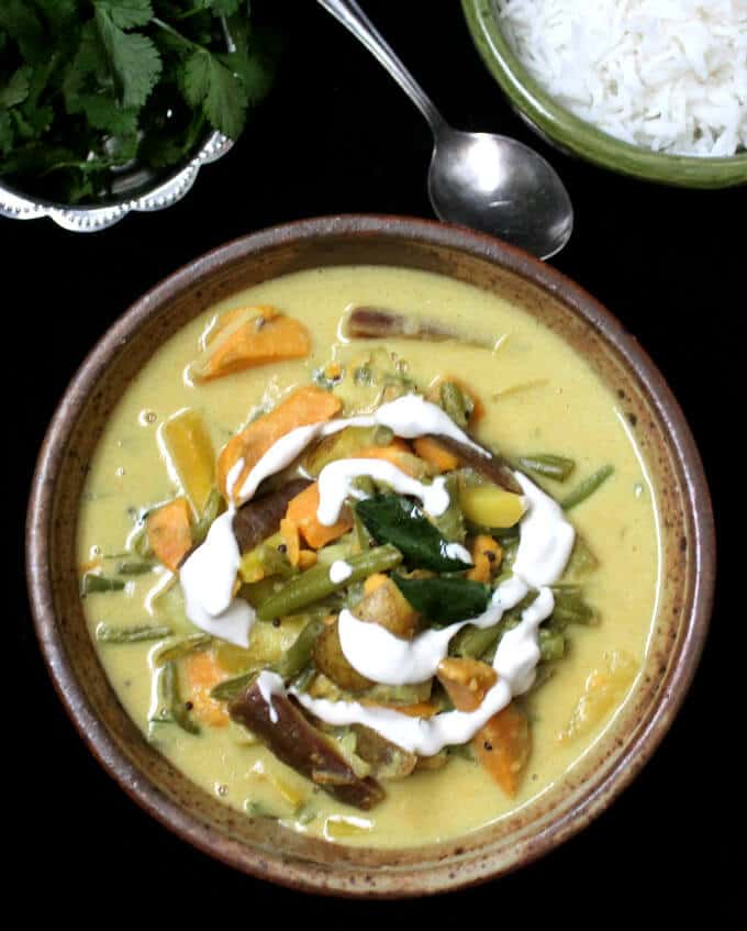 Photo of Avial or south Indian vegetable curry served with rice and cilantro garnish.