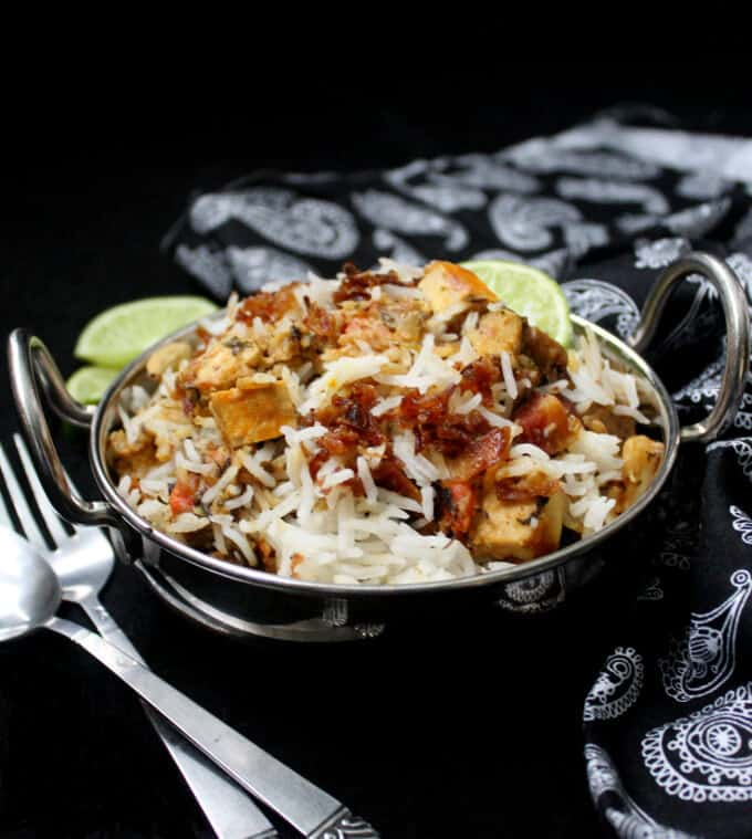 Vegetarian biryani in a steel karahi with tofu cubes, lemon slices and fried onions and with a fork and spoon