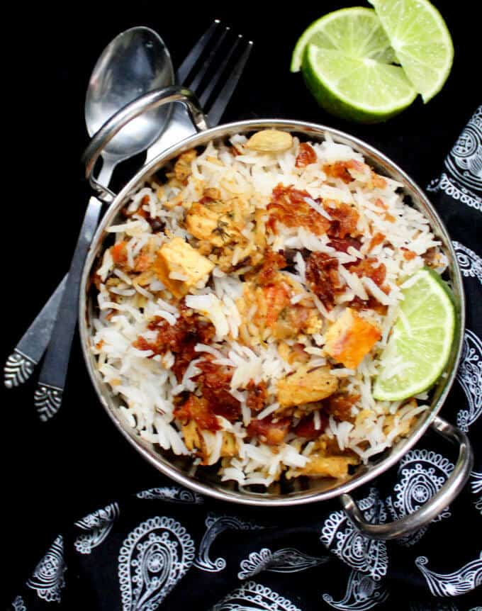 Overhead shot of veg biryani in a steel karahi with tofu cubes, lemon slices and fried onions and with a fork and spoon