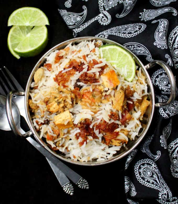A top shot of vegan vegetable biryani in a steel karahi bowl with tofu cubes, fried onions, lemons and silverware and a black napkin with a paisley print.