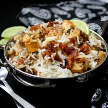 Vegetable biryani with tofu cubes, onions, limes and biryani masala in a steel karahi bowl with a spoon and fork.