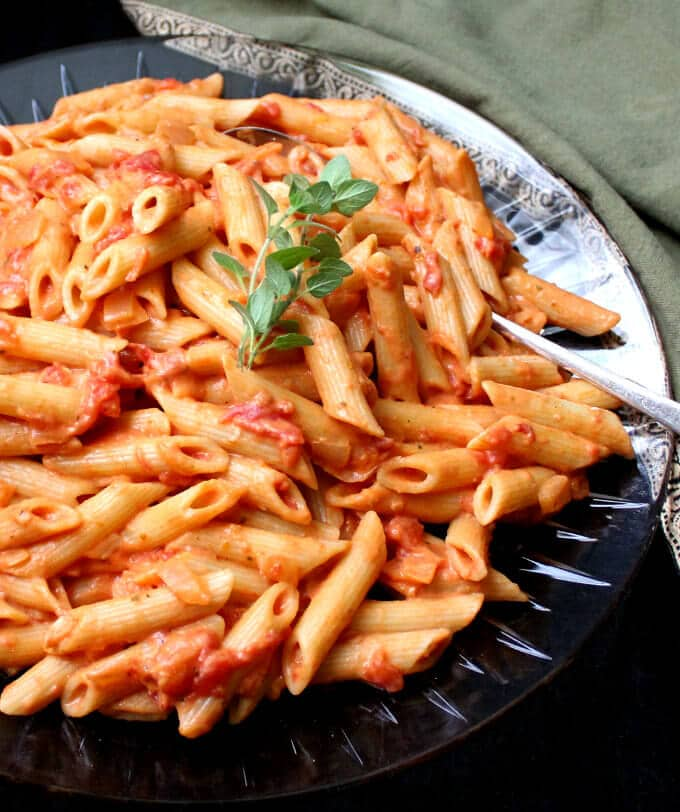 Partial shot of a big crystal platter of vegan vodka pasta with a serving spoon, oregano and a green and gold napkin.