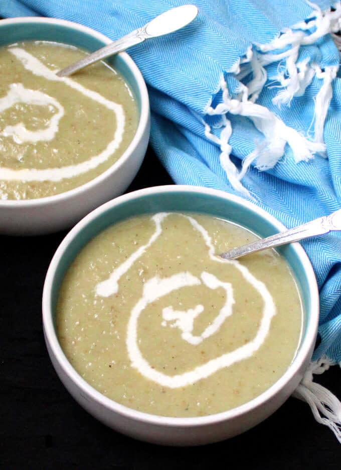 Vegan Irish Leek and Potato Soup with a cashew cream ganish in blue and white bowls with soup spoons and a blue napkin behind.