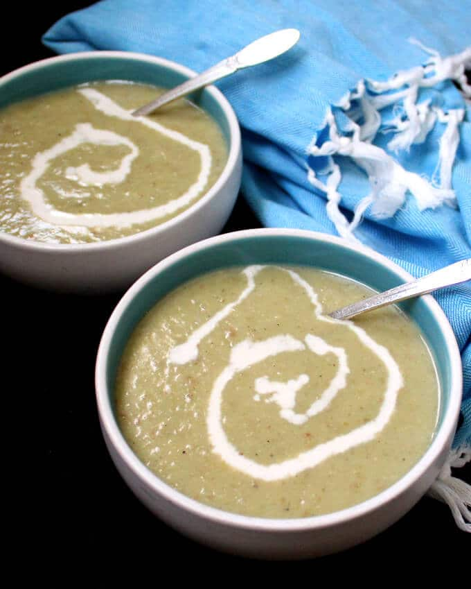 Photo of Vegan Irish Leek and Potato Soup with a cashew cream ganish in blue and white bowls with soup spoons and a blue napkin behind.