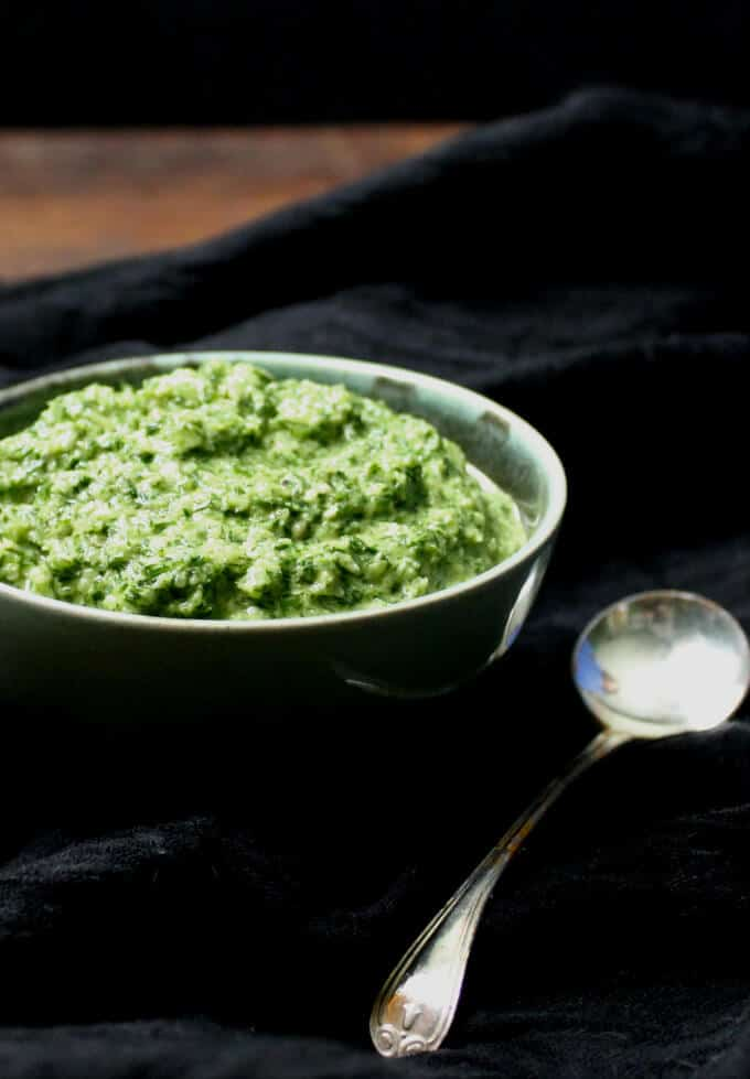 A fresh and green Fennel Fronds Pesto in a blue-green bowl with a silver spoon on a black cheesecloth