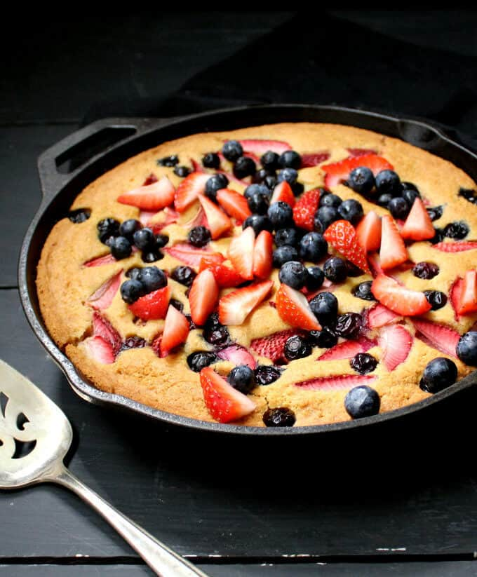 A glutenfree vegan Skillet Cornbread Cake that's golden and tender and delicious, with fresh berries baked in. #vegan #glutenfree #nutfree #soyfree #cake #mothersday HolyCowVegan.net